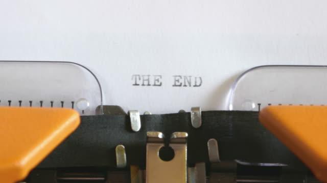 aufnahmen von einer person schreiben the end auf einer alten schreibmaschine mit sound hautnah - storytelling videos stock-videos und b-roll-filmmaterial