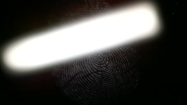 Close up footage of a scanner analyzing a fingerprint left on a surface