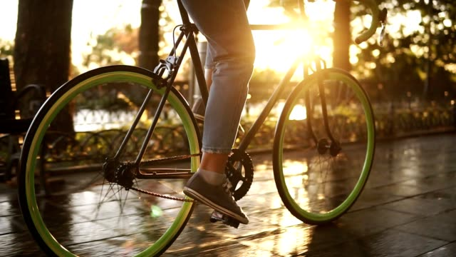 close up footage of female feet cycling a bicycle in the morning park or boulevard. side view of a young woman riding a trekking bike, wearing sneakers and jeans. sun shines on the background - veicolo a due ruote video stock e b–roll