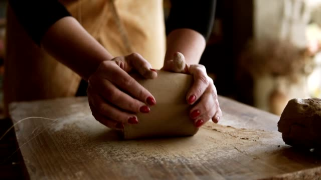 close up footage of female hands with beautiful red manicure holding clay and kneading it on a worktop. wearing beige apron. unrecognizable person. soft clay - скульптура стоковые видео и кадры b-roll