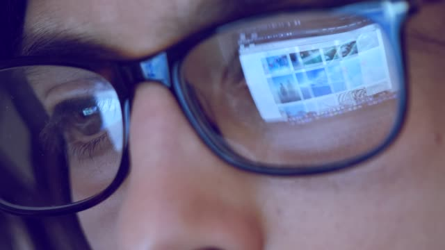 Close up footage of female with glasses looking at computer