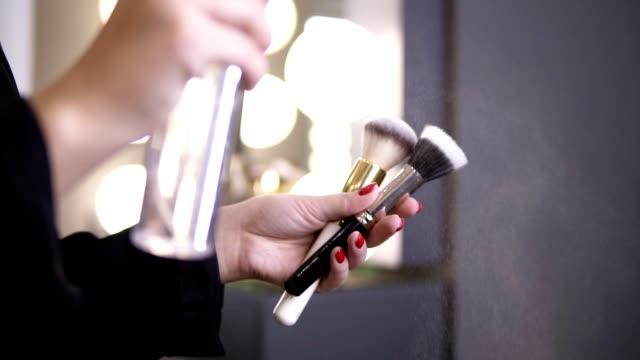 vidéos et rushes de fermez les images des mains d'artistes de maquillage et des lampes blanches lumineuses sur le fond: préparation de deux brosses avec le spray de nettoyage. femme et cosmétiques. ralenti - pinceau à maquillage