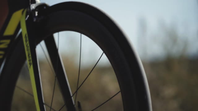 Close up footage of male triathlete feet cycling a bicycle in the morning, in a sunny day. Road bike detailed close up shot