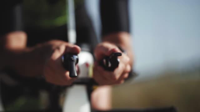 da vicino le riprese dei piedi triatleti maschi che pedalano in bicicletta al mattino, in una giornata di sole. colpo ravvicinato dettagliato della bici da strada - ciclismo su strada video stock e b–roll