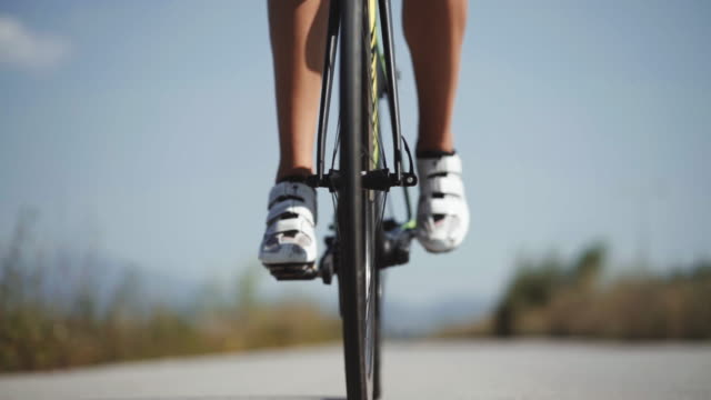 close up footage of male triathlete feet cycling a bicycle in the morning, in a sunny day. road bike detailed close up shot - evento ciclistico video stock e b–roll
