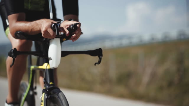 close up footage of male triathlete feet cycling a bicycle in the morning, in a sunny day. road bike detailed close up shot - veicolo a due ruote video stock e b–roll