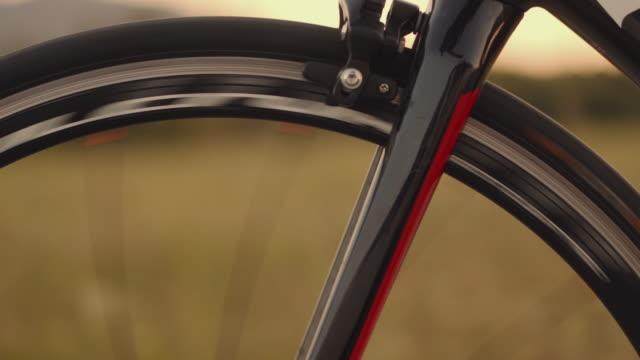 da vicino le riprese dei piedi triatleti maschi che pedalano in bicicletta la sera, in una giornata di sole. bici da strada dettagliato primo piano girato durante il tramonto - ciclismo su strada video stock e b–roll