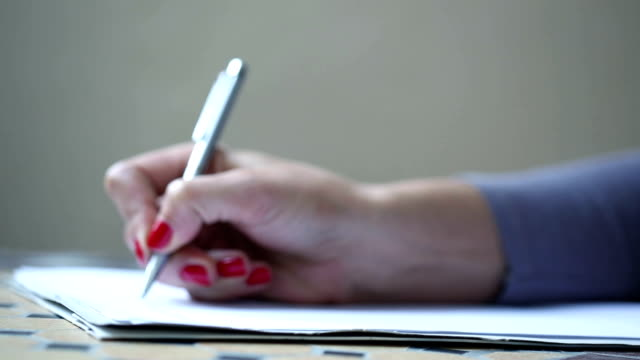 Close up footage of woman hand, handwriting with silver metal pen video