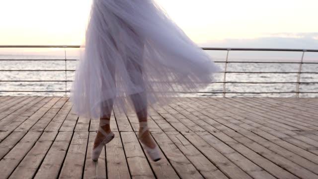 närbild bilder av unga ballerinas ben i dans rörelse. balettdansös i långa vita tutu och pointe utöva utomhus, trägolv. dagtid - piruett bildbanksvideor och videomaterial från bakom kulisserna