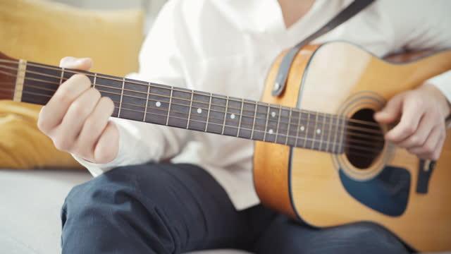 4k primi filmati di giovani chitarristi che improvvisano alla chitarra acustica, raccolgono corde diverse e prendono accordi diversi - braccio umano video stock e b–roll