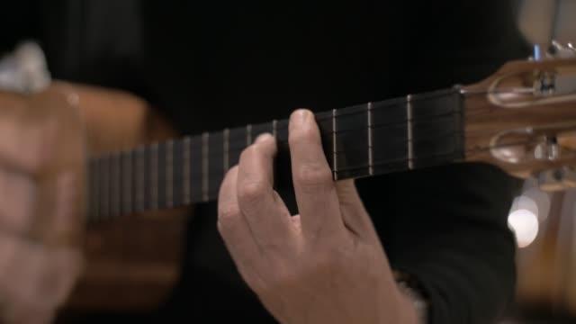 vídeos de stock, filmes e b-roll de feche para um instrumento musical folk de quatro cordas - música acústica