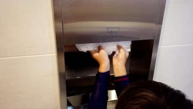 Close up for hands boy's hand pulled the toilet paper in the toilet.
