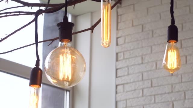 白いレンガの壁を持つ部屋の天井から黒いワイヤーにぶら下がっている異なる形態の導かれた電球のためにクローズアップ。メディア。木の枝に美しいレトロな電球、家の装飾要素 ビデオ