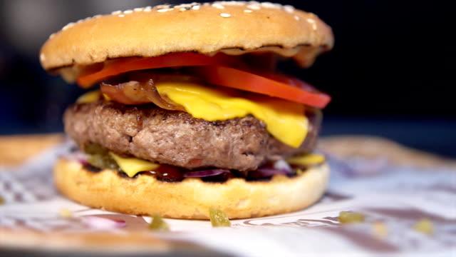 close up freshly prepared cheeseburger burger hamburger. tasty and appetizing hamburger cheeseburger - płyta do pieczenia filmów i materiałów b-roll