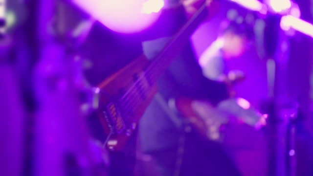 Close up front shot a bass while musician plays music. Man bass guitarist playing electrical guitar on concert stage rock music stock videos & royalty-free footage