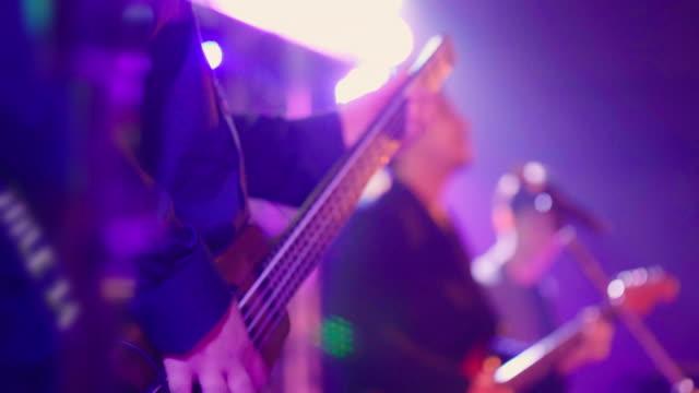 vidéos et rushes de fermez-vous vers le haut du projectile avant une basse tandis que le musicien joue la musique. - art du spectacle