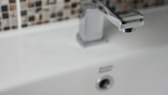 4K Close up frontal shot off dripping tap. Dripping faucet. Leakage and water saving concept. 4K Close up frontal shot off dripping tap. Dripping faucet. Leakage and water saving concept. water wastage stock videos & royalty-free footage