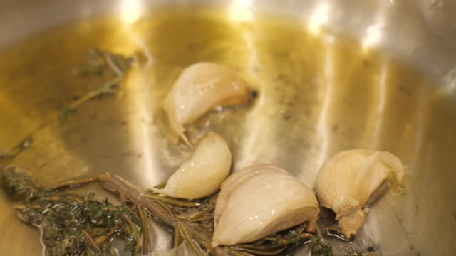 Close up garlic cloves fried in oil with spices and herbal in oil on frying pan - video