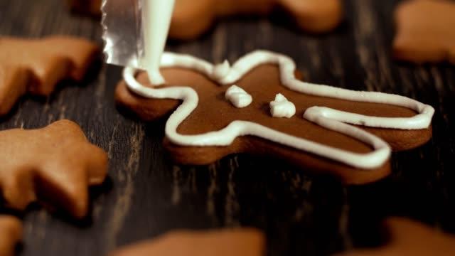 Close up garnishing gingerbread men. Decoration process of Christmas cookies.