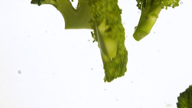 Close up green broccoli thrown floating in water