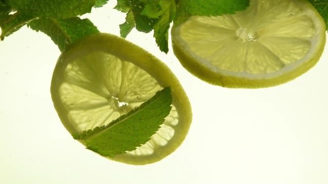 vídeos de stock, filmes e b-roll de close-up de folhas de hortelã verde e limão em mojito - tea drinks