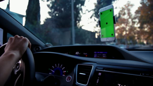 close up green screen cell phone while driving - autista mestiere video stock e b–roll
