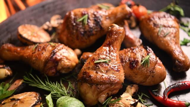 vídeos de stock, filmes e b-roll de feche a grelha assada perna de frango churrasco com ervas adicionais e especiarias na frigideira na grelha flamejante . - antepasto