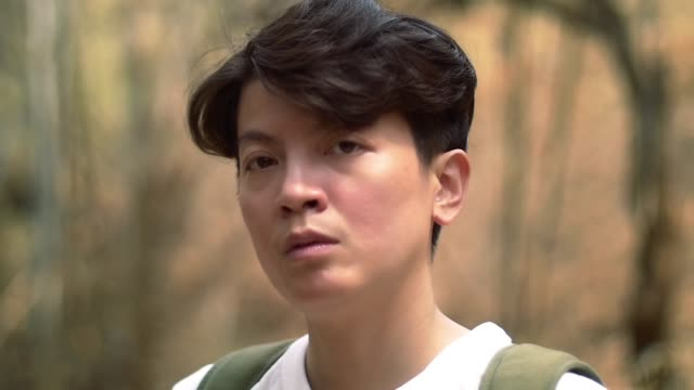 close up guy face looking at the camera in the forrest meaningful expression video