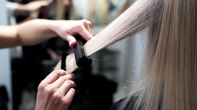 クローズアップ、美容師スタイリング長ブロンド女性の髪とヘアストレートナー - ブラシ点の映像素材/bロール