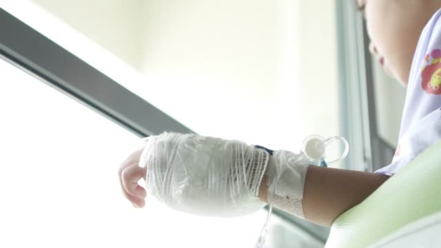Close up hand bandaged of sick asian child girl in the hospital. Real time shot in treatment room. video