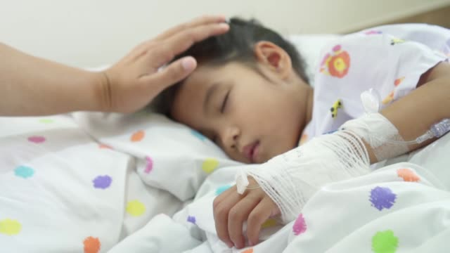 Close up hand bandaged of sick asian child girl while she is sleeping on bed in the hospital and young mother is touching her head in blurred. video