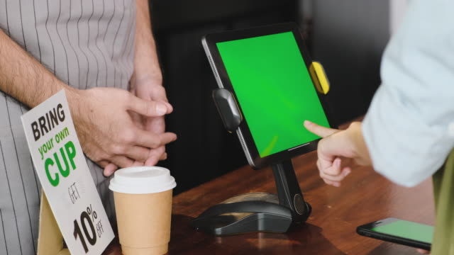 close up hand customer order coffee on green screen tablet menu at counter bar in cafe.