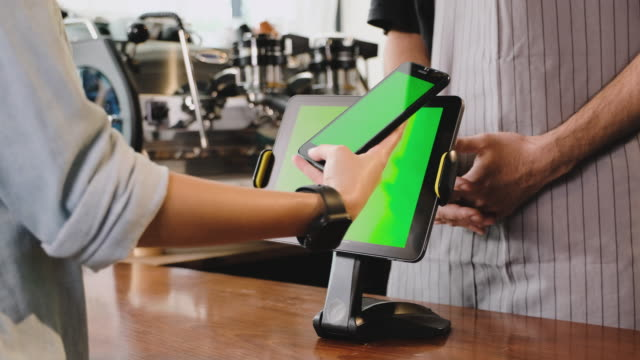 close up hand customer use mobile e wallet app paying contactless on green screen tablet at counter bar in cafe.wireless payment nfc lifestyle