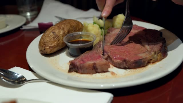 close up hand cuts into prime rib meal at restaurant video