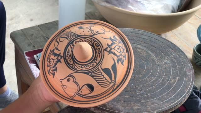Close up hand decorating pottery Celadon, sukhothai thai art,making Thai ceramics handicraft