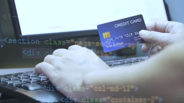 close up hand hold credit card and key in on keyboard with coding overlay . - credit card filmów i materiałów b-roll