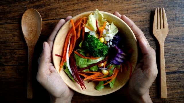 テーブルの上の木製のボウルにカラフルな野菜を混ぜたクローズアップハンドホールド、ダイエットと減量を制御するためのビーガン健康的なオーガニック食品 - ベジタリアン料理点の映像素材/bロール