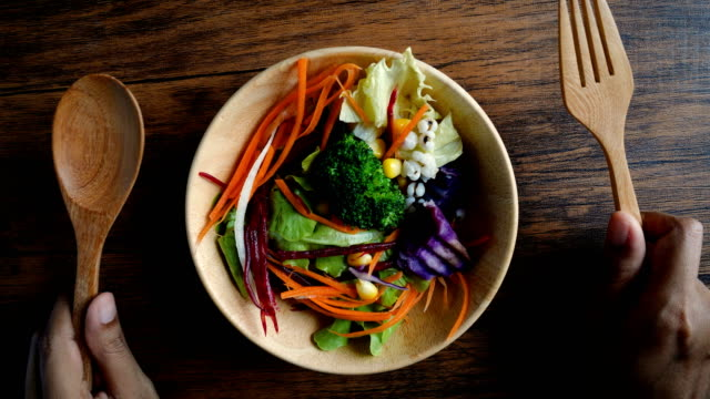 Close up hand hold mixed of colorful vegetable in wooden bowl on the table , vegan healthy organic food for diet and control weight loss