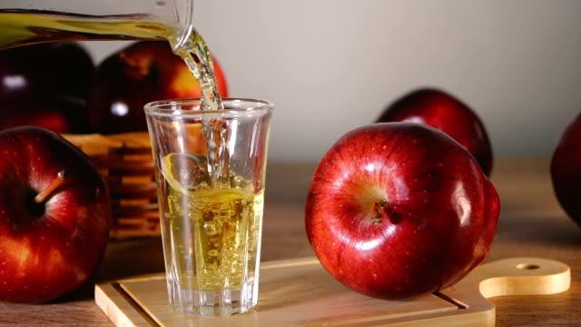 손을 잡고 테이블에 붓는 사과 사이 다 식초, 체중 감량을 위한 건강 한 음식, 콜레스테롤 감소, 낮은 혈당 수치 - 식초 스톡 비디오 및 b-롤 화면