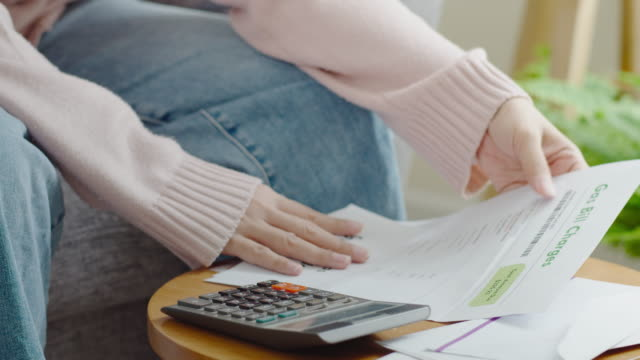 Close up hand of asian woman holding bill payment and calculataion via calculator at home feeling anxiety depression upset frustrated thinking about personal financial crisis money problem concept.