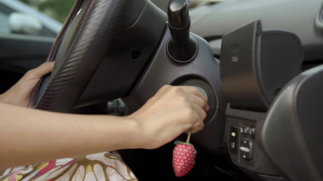 Close Up Hand of Asian Woman Using Key Start Engine of Car.