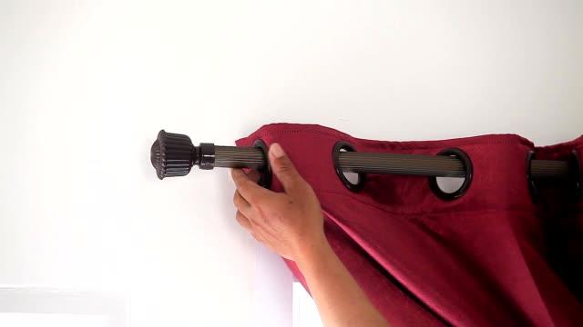 stockvideo's en b-roll-footage met close-up hand van technicus rode gordijnen installeren via de windows in huis. - hangen