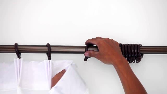 zamknij rękę technika instalując czerwone zasłony nad windowsem w domu. - wisieć filmów i materiałów b-roll
