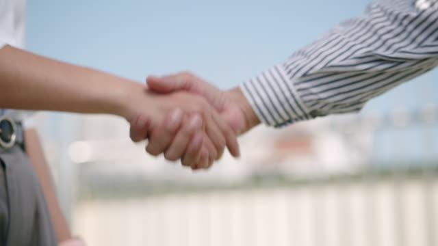 nahaufnahme. hand von zwei asiatischen geschäftsleuten, die sich zum handschlag versammelt haben, stimmen einem deal zu oder sagen hallo in der großstadt. - reliability stock-videos und b-roll-filmmaterial