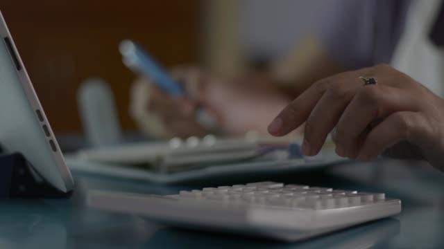 närbild hand kvinna kontrollera kontosaldo och beräkna kostnader i vardagsrummet hemma. hemmafru arbetar med kalkylator och notera på skrivbordet under karantän med covid-19 pandemi situation. - dept bildbanksvideor och videomaterial från bakom kulisserna
