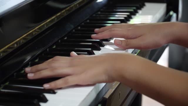 Close up hand playing piano.
