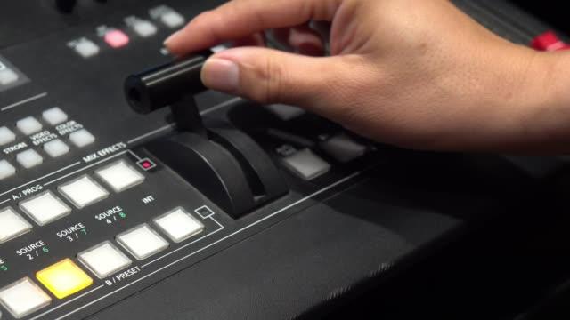 vidéos et rushes de fermez-vous vers le haut de la main tirant sur un commutateur vidéo, télévision de diffusion. - interview