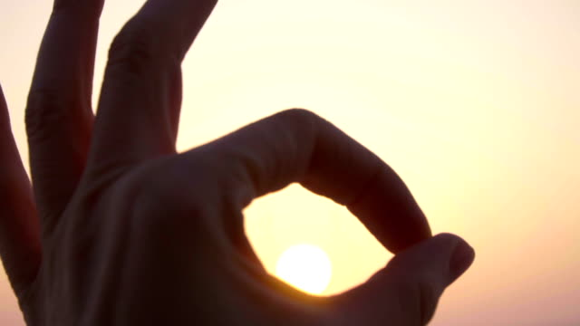 close up hand showing gesture sign symbol ok in slow motion against sunset sky - emblema video stock e b–roll
