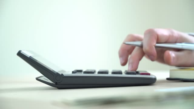 Close up hand using calculator and financial statements