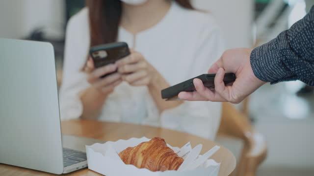 レストランで非接触決済で携帯電話を使用して手をクローズアップ - クレジット決済点の映像素材/bロール